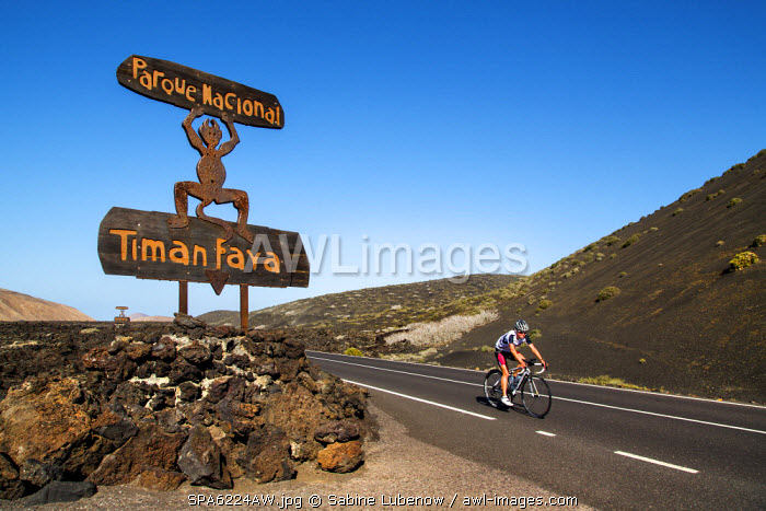 Cyclist and road sign, Timanfaya national park, Lanzarote, Canary Islands, Spain