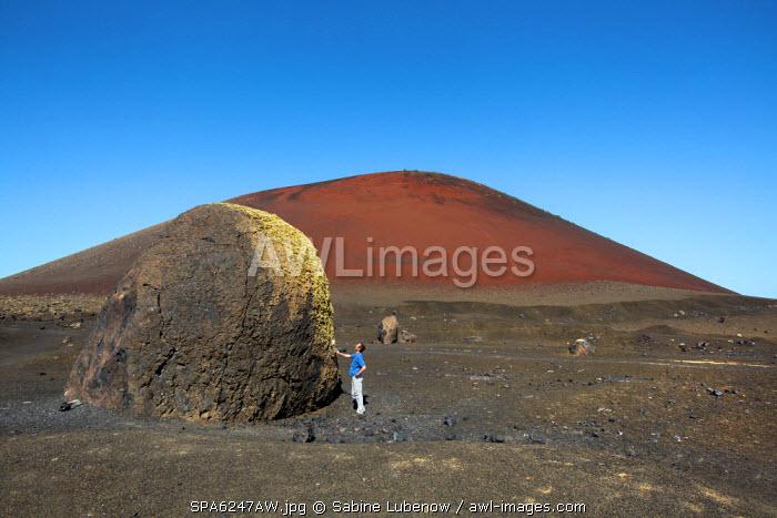 Hiker and volcanic bomb, Caldera Colorada, Parque de los Volcanes, Lanzarote, Canary Islands, Spain