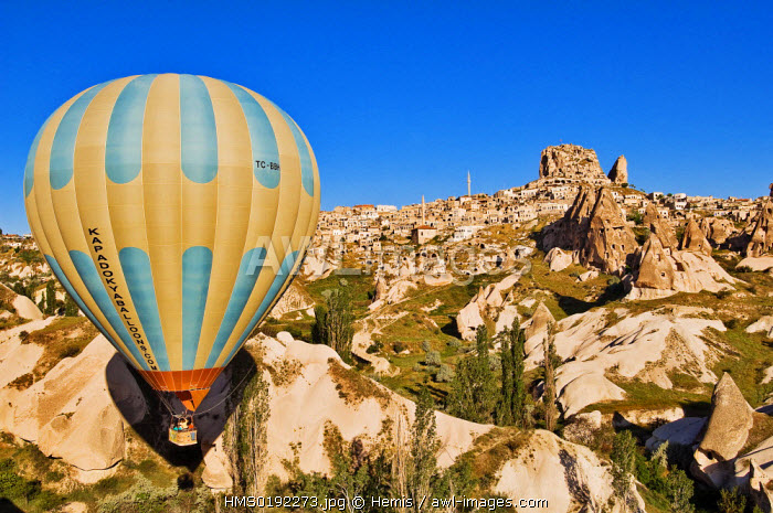 Turkey, Central Anatolia, Cappadocia, listed as World Heritage by UNESCO, Uchisar village, balloons in front of hills of tuff and cave dwellings