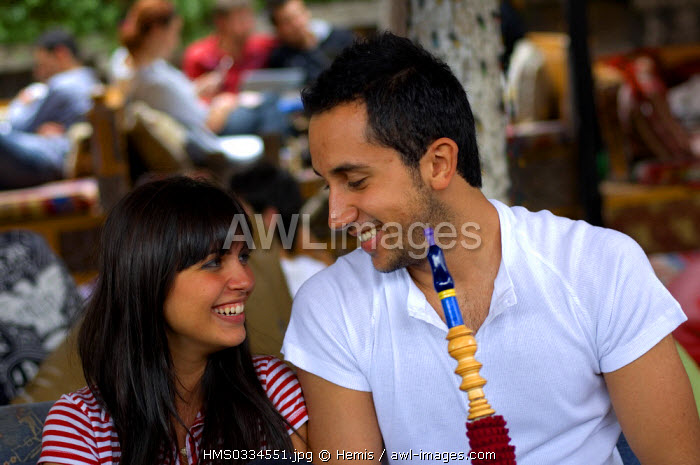 Turkey, Istanbul, Tophane District, young couple smoking hookah