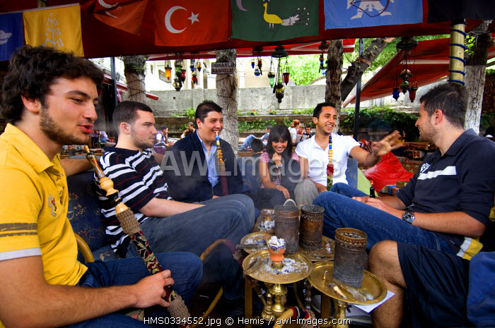 Turkey, Istanbul, Tophane District, group of young people smoking hookah