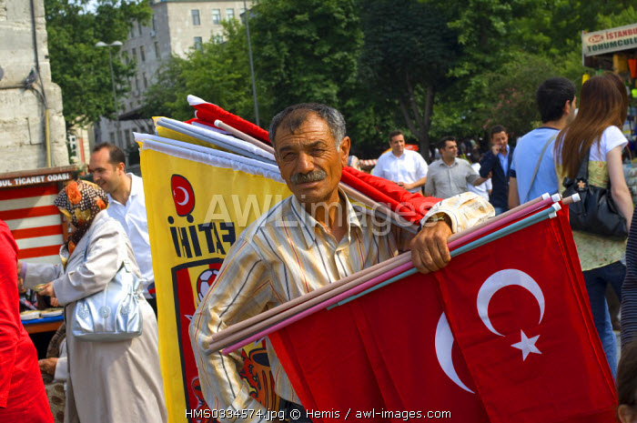 Turkey, Istanbul, historical centre listed as World Heritage by UNESCO, flags salesman in front of Yeni Cami (New Mosque)