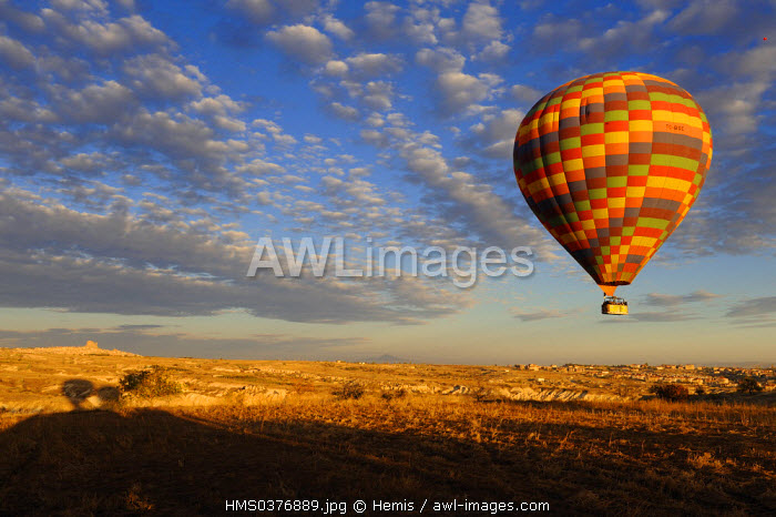 Turkey, Central Anatolia, Nevsehir Province, Cappadocia listed as World Heritage by UNESCO, hot air baloon flying over and Uchisar Rock in the background