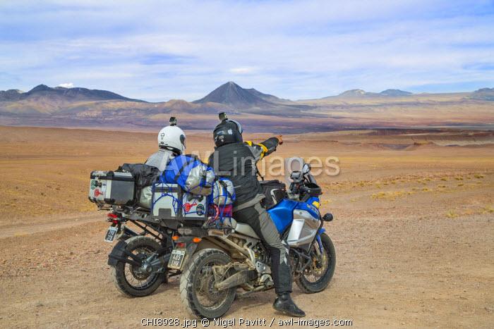 Chile, Atacama Desert, Antofagasta Region, El Loa Province. Two motorcyclist pause to admire the view of the Atacama Desert near San Pedro de Atacama, a small oasis town.