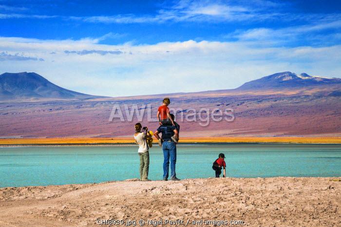 Chile, Atacama Desert, Salar de Atacama, Laguna Tebenquiche, Antofagasta Region, El Loa Province. A family admires the beautiful Laguna Tebenquiche which is situated on the salt flats of the Atacama Desert.