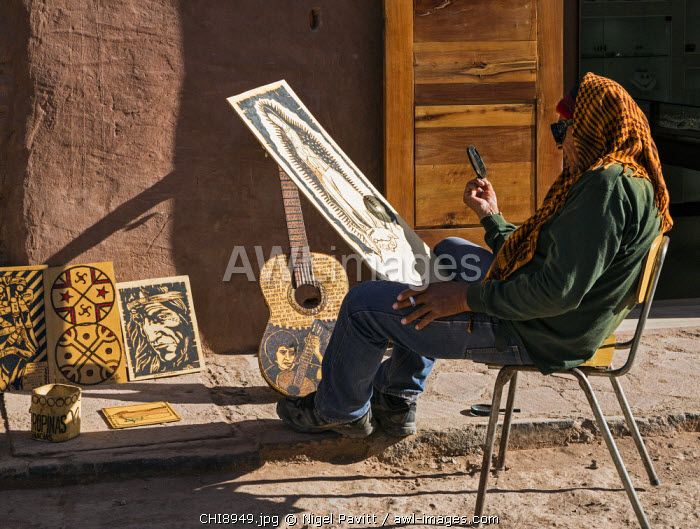 Chile, San Pedro de Atacama, Antofagasta Region, El Loa Province. An artist in San Pedro de Atacama using the power of the sun with the aid of a magnifying glass to burn a picture of the Virgin Mary onto treated wood.