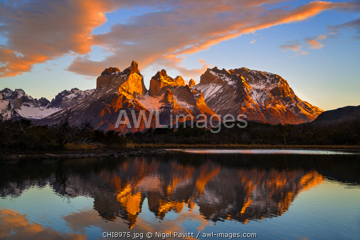 Chile, Torres del Paine, Magallanes Province. Sunrise over Torres del Paine reflected in the waters of Lake Pehoe in the foreground. One of the principal attractions of the National Park is the magnificent Paine massif.