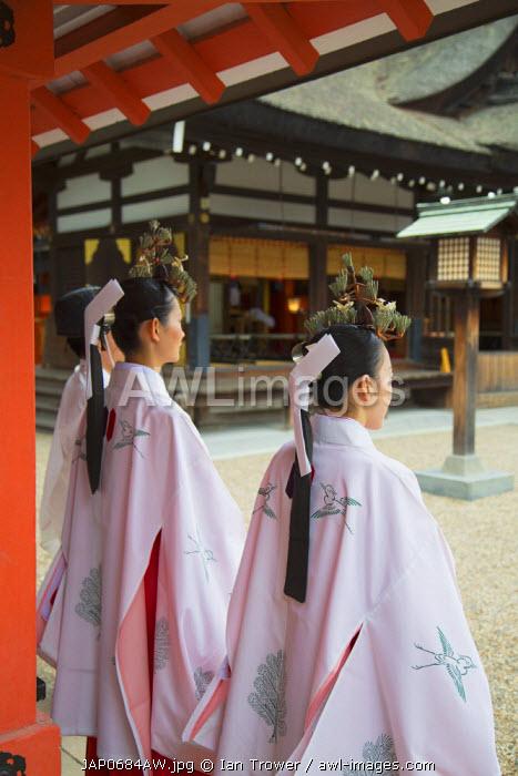 Shrine maidens and priest at traditional wedding ceremony at Shinto shrine of Sumiyoshi Taisha, Osaka, Kansai, Japan