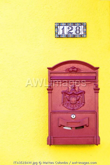 Italy, Veneto, Venice, Burano. Letterbox on yellow wall