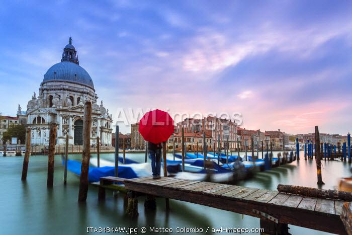 Italy, Veneto, Venice. Santa Maria della Salute church on the Grand Canal, at sunset, woman standing with red umbrella (MR)