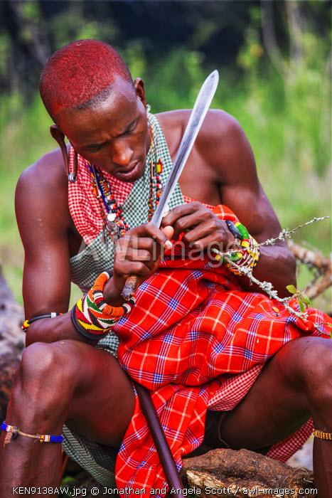 Africa, Kenya, Narok County, Masai Mara. A Maasai man carving with a knife.