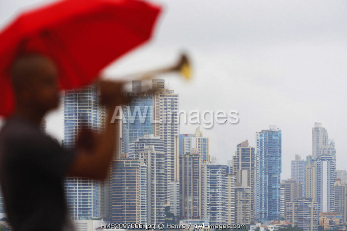Panama, Panama City, horizontal view of a modern part of Panama City with a street performer playing the trumpet in the foreground
