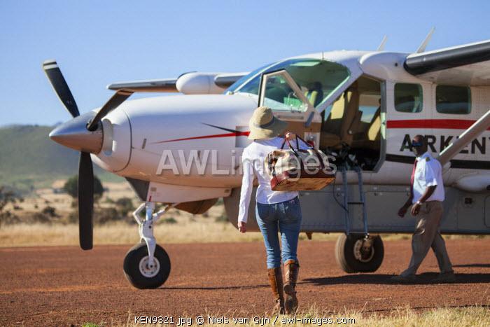 Kenya. A tourist walks towards her waiting plane.
