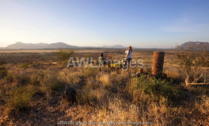 Kenya, Shaba National Park. A couple enjoy a sundowner overlooking the plains of Shaba National Reserve. MR