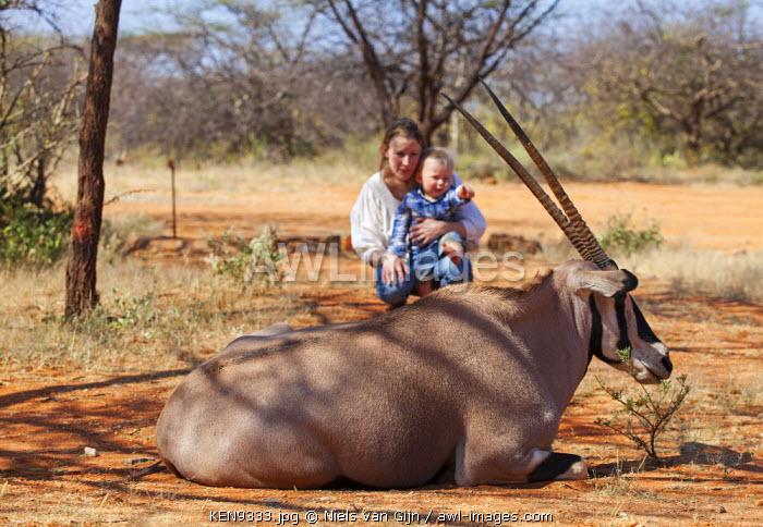 Kenya, Shaba National Park. A mother and child watch a habituated Oryx near Shaba National Park.