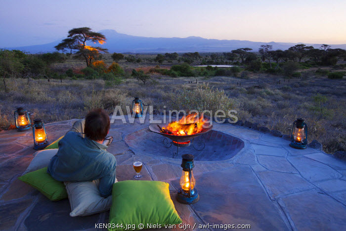 awl-images.com - Kenya / Kenya, Amboseli National Park, Tortilis Camp. A guest relaxes with a beer, overlooking Mount Kilimanjaro. MR.