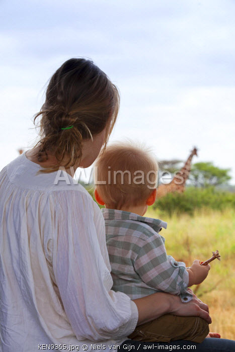 Kenya, Meru National Park. A young boy clutches his toy giraffe as he stares at the real thing. MR.