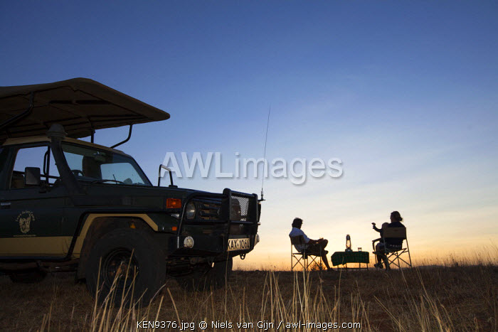 Kenya, Lewa Conservancy. Silhouetted guests enjoying a sundowner.