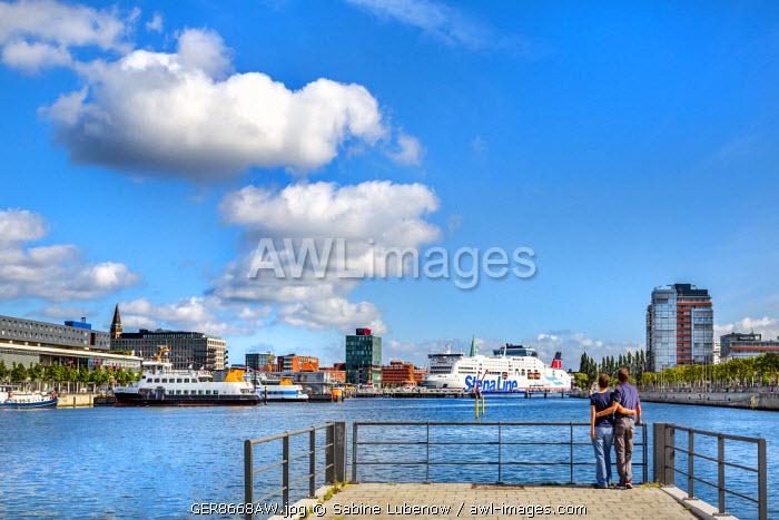 Couple looks towards the city, Kiel, Baltic coast, Schleswig-Holstein, Germany
