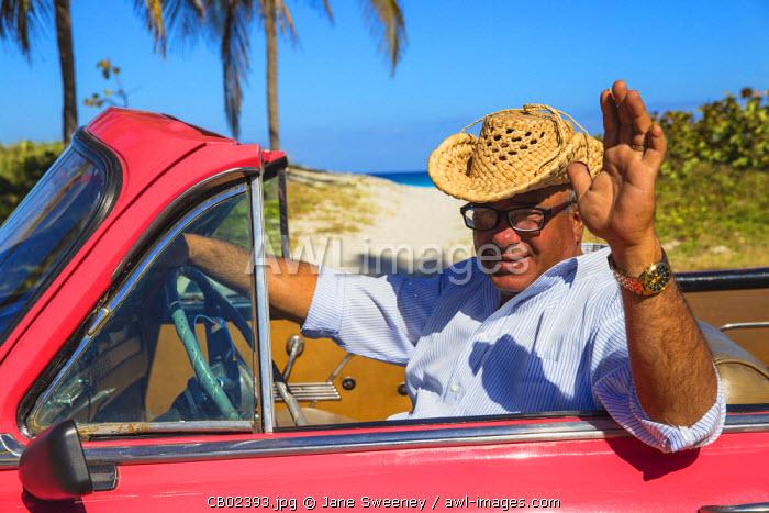 Cuba, Varadero, Man in Pink Plymouth car waving on Varadero beach