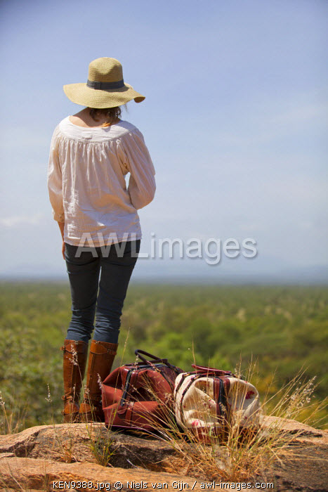 awl-images.com - Kenya / Kenya, Meru National Park. A young lady stands with her luggage, overlooking Meru National Park. MR.
