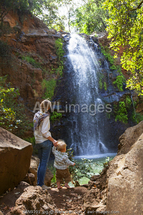 Kenya, Lewa Conservancy. A mother and child look at a rushing waterfall in the Ndare Ngare Forest. MR.