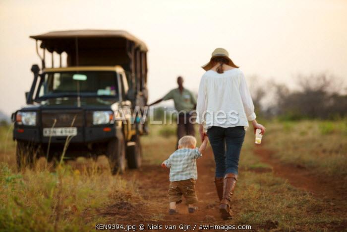 Kenya, Meru National Park. A mother and son make their way back to the safari vehicle. MR.