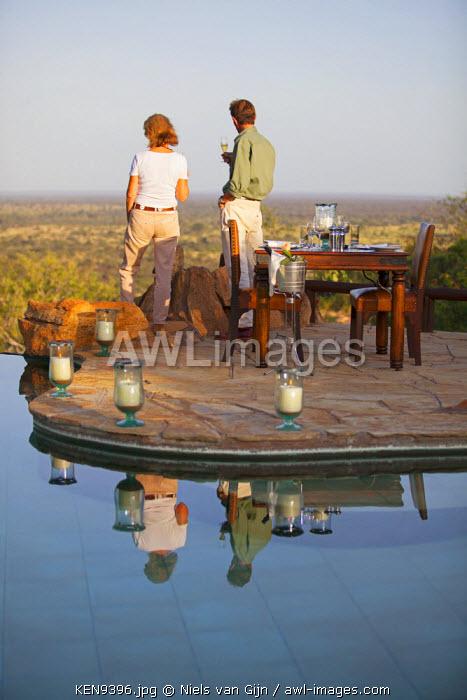Kenya, Meru National Park, Elsa's Kopje. A couple enjoy a sundowner, overlooking the views of Meru National Park.