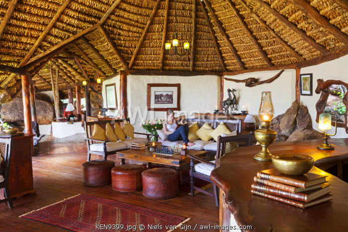 Kenya, Meru National Park, Elsa's Kopje. A guest relaxes on the sofa in Elsa's Kopje. MR.