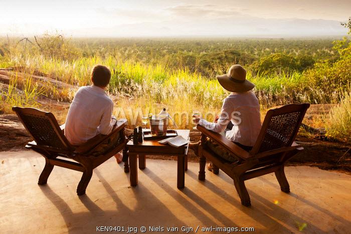 Kenya, Meru National Park, Elsa's Kopje. A couple enjoy an evening drink overlooking Meru National Park. MR.
