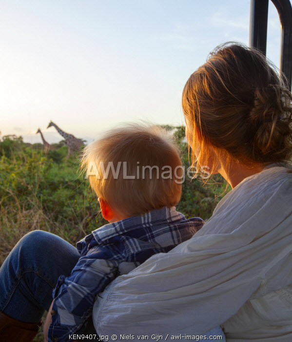 awl-images.com - Kenya / Kenya, Meru National Park. A mother and child watch giraffe on a game drive. MR.