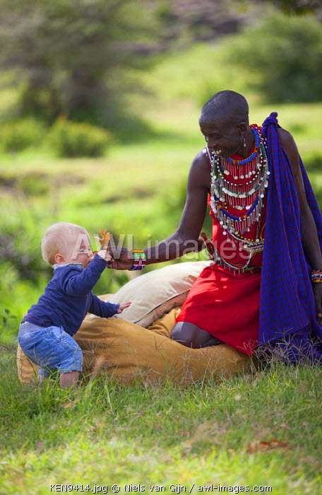 Kenya, Mara North Conservancy. A young guest plays with a Maasai guide. MR.