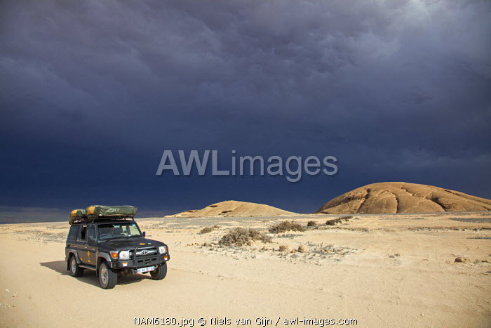 Namibia, Namib-Naufluft National Park. An expedition 4x4 drives through the desert ahead of an approaching storm.