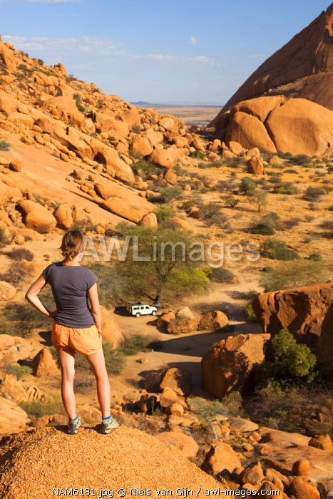 Namibia, Spitzkoppe. A woman climbs to the top of a kopje for a view over the vast landscape. MR.