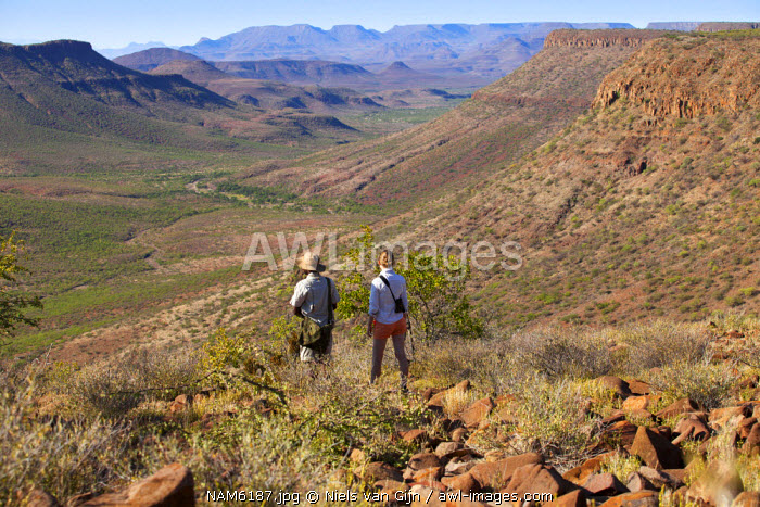 Namibia, Grootberg. A tourist and her guide on a trek stop to look over the vast Grootberg valley. MR.