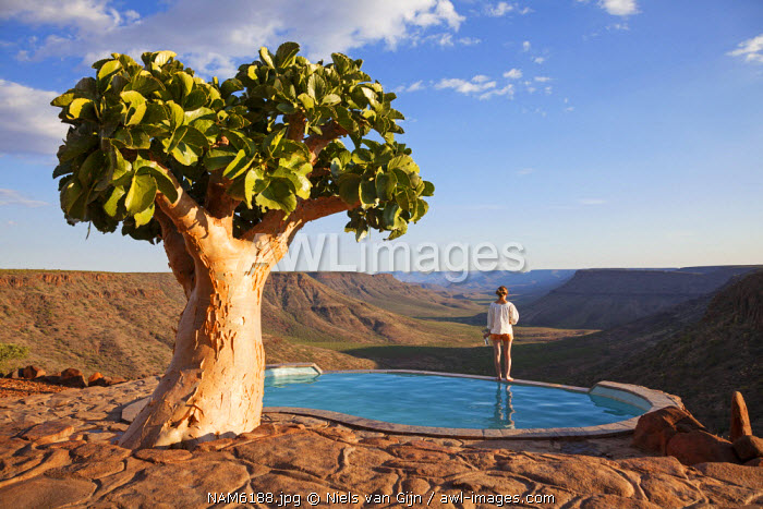 Namibia, Grootberg. A woman enjoys the evening views overlooking the Grotoberg valley. MR.