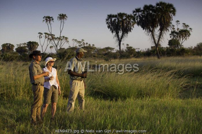 Kenya, Meru. A couple enjoys a sundowner with their guide in Meru National Park