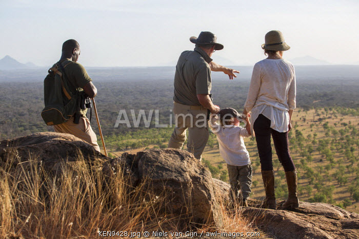 Kenya, Meru. A young family and their guide look out over Meru National Park during a walking safari.