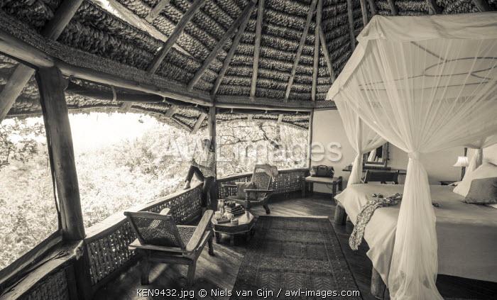 Kenya, Meru. A woman looks out over Meru National Park from her luxury room at Elsa's Kopje. MR.