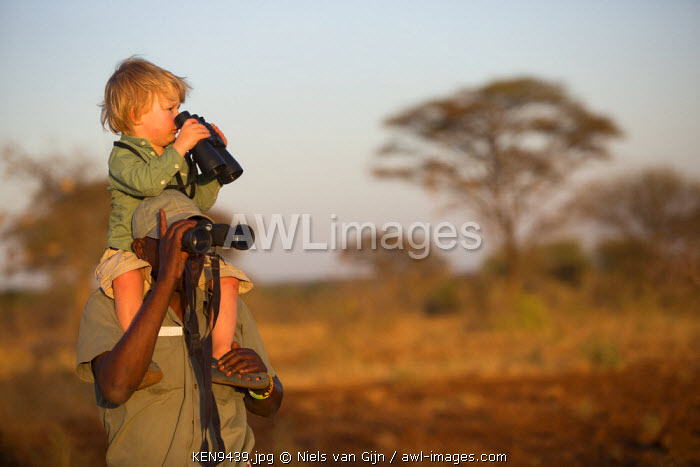 awl-images.com - Kenya / Kenya, Meru. A young boy and a guide search for wildlife in Meru National Park.