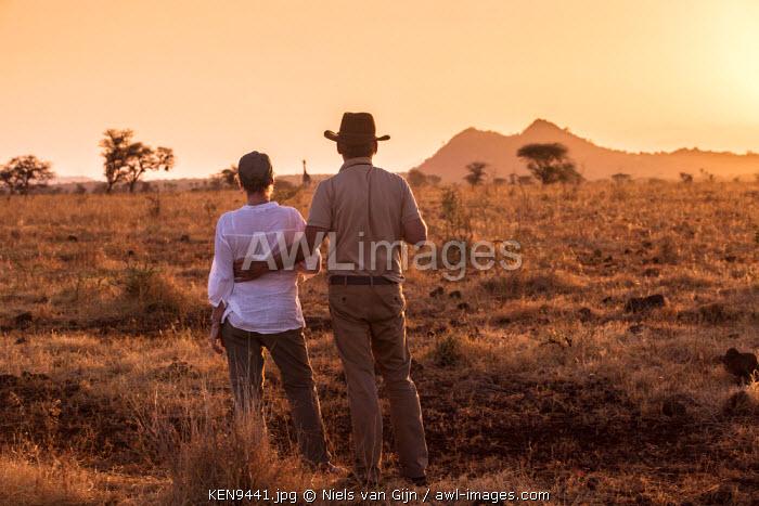 Kenya, Meru. A couple enjoy a sundowner, looking out towards a lone giraffe. MR.