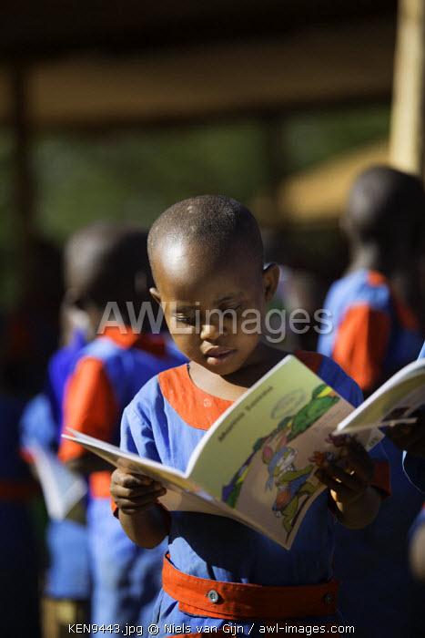 Kenya, Meru. A young schoolgirl reads a book.