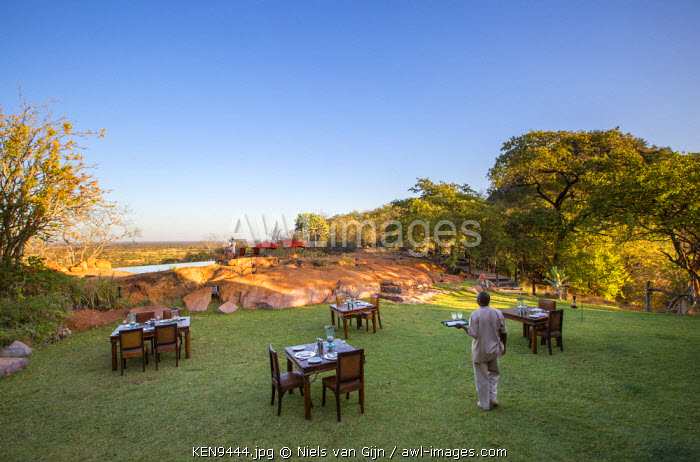 Kenya, Meru. A waiter takes drinks out to a couple by the pool.