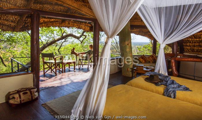 Kenya, Meru. A lady relaxes on the balcony of her luxury safari room. MR.