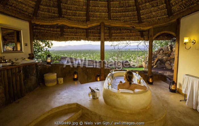 Kenya, Meru. A woman relaxes in a huge bath, enjoying the views over Meru National Park. MR.