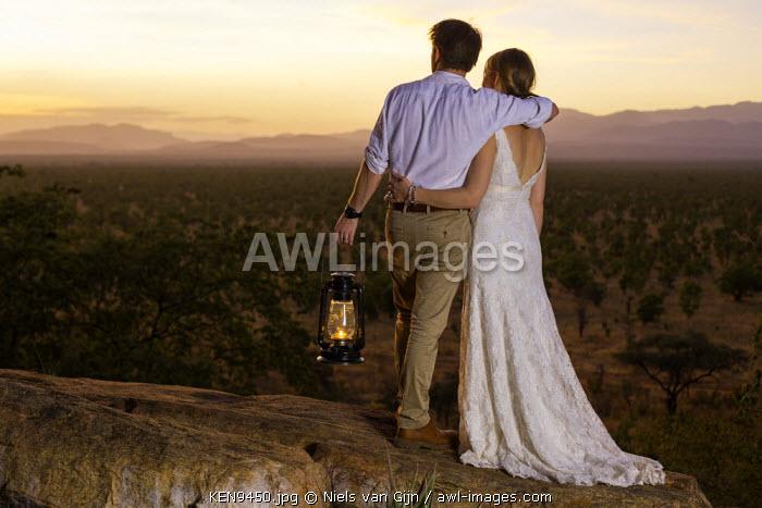 Kenya, Meru. A young newly-wed couple watch the sun set over Meru National Park. MR.