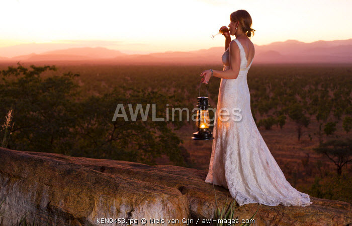 Kenya, Meru. A new bride enjoys a glass of Champagne, watching the sun set over Meru National Park. MR.