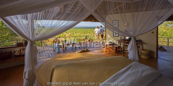 Kenya, Meru. A couple stands on the balcony of a luxury safari room overlooking Meru National Park. MR.