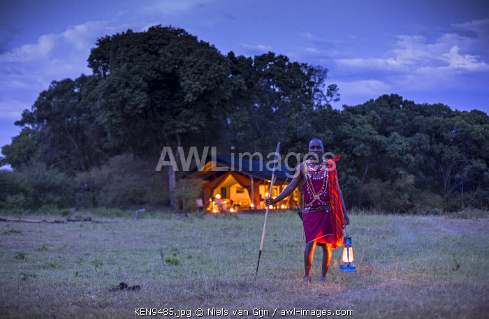 Kenya, Mara North Conservancy. An askari guide ready to escort his guests to their tent at Elephant Pepper Camp.