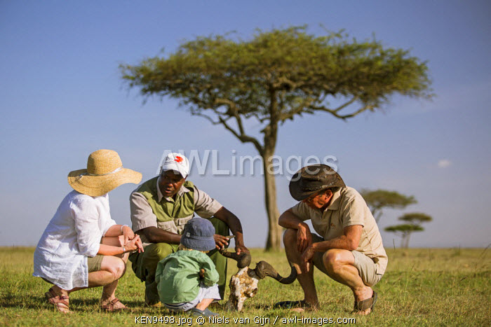 Kenya, Mara North Conservancy. A family learn about the bush from their guide.